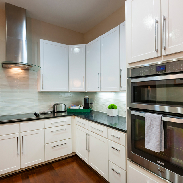 White kitchen with steel appliances at Ascent at City Centre Apartments in Houston